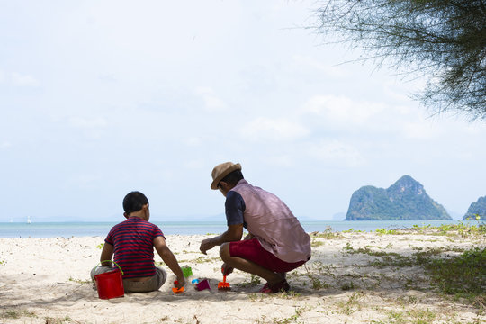 Father and son with the beach,They are playing sand so happily.