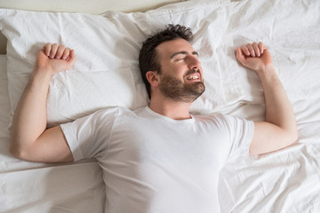 Man , bedtime and rest concept . Man lying in bed at home