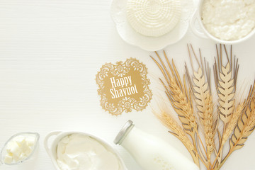 Top view image of dairy products over white wooden background. Symbols of jewish holiday - Shavuot.