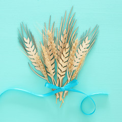 top view of wooden wheat crop decoration over mint background. Symbols of jewish holiday - Shavuot.