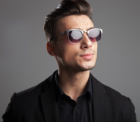 portrait of handsome fashion man with sunglasses looking to side