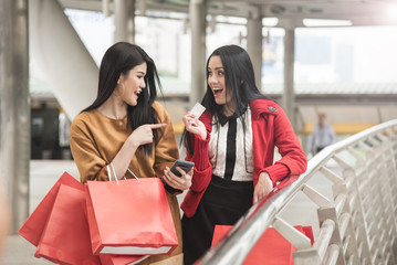 Beautiful girls holding shopping bags using a smart phone with credit card and smiling while standing outdoor.