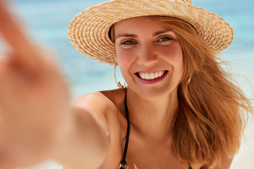 Attractive young woman with broad smile, healthy skin, rests on seashore, takes photo of herself, being in good mood, enjoys leisure and summer vacation. Beautiful female makes selfie against ocean