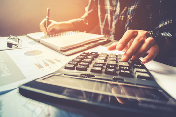 Businessman's hands with calculator at the office and Financial data Cost Economic