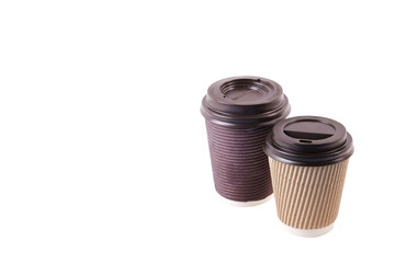 A pair of brown carton double walled paper cups, take out, coffee to go. Two colorful eco-friendly heat resistant cardboard mugs for hot beverages w/ cap, isolated, background, close up, copy space.