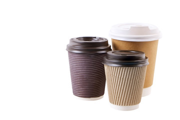 Three brown carton double walled paper cups, different sizes, take out, coffee to go. Disposable eco-friendly cardboard mugs for hot beverages w/ cap, isolated white, background, close up, copy space.
