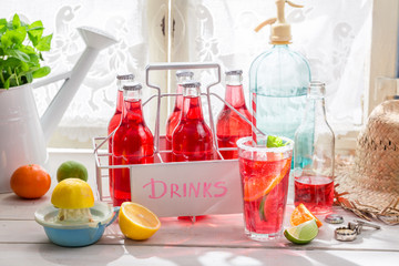 Red orangeade in bottle with citrus fruit on white table