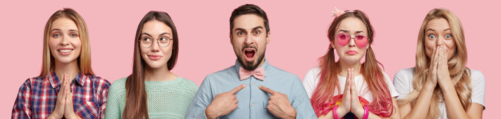 Irritated bearded male indicates at formal shirt, stands between beautiful women who express different emotions, isolated over pink background. Two females plead as keep palms pressed together