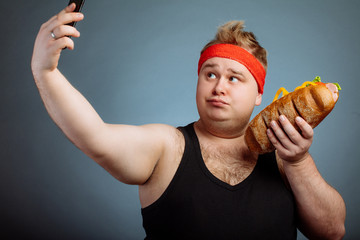 Fat funny man with sandwich in hand makes selfie