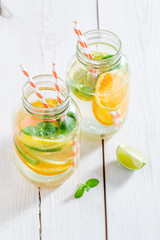 Water with mint leaves and citrus fruits on white table