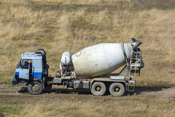 Moving concrete mixer truck on dirty dusty empty field road. Building, delivering and transportation concept.