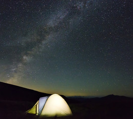 Tourist hikers tent in mountains at night with milky way stars in the sky