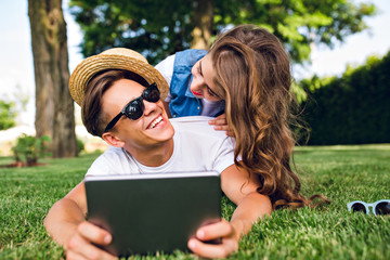 Pretty girl with long curly hair and red lips is lying on back of handsome guy in sunglasses on grass in summer park. Guy holds tablet, girl is laughing to him.