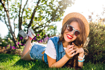 Pretty girl with long curly hair in hat is lying on grass in summer park. on sunlight. She wears jeans jerkin,  shorts, sunglasses. She is smiling to camera with red lips.