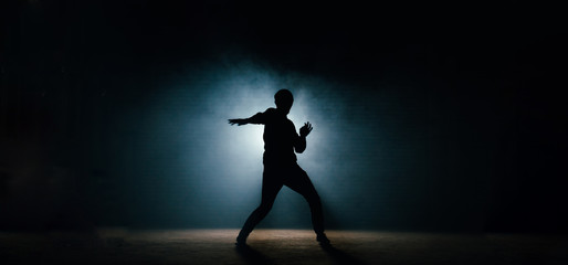 young man in casual clothers showing his dance on the dark street. night show. night dance. dansing pose
