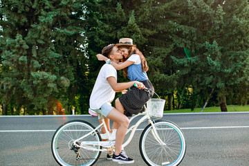 Full-length photo of young couple in love on bike on road on forest background. Handsome guy is driving a bike and kissing a  girl with long curly hair in hat sitting on the handlebars.