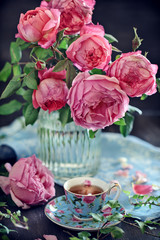 Delicate beautiful pink roses from a garden in a glass vase. English Roses,Variety -  Princess Alexandra of Kent. And a tea in a beautiful porcelain cup.