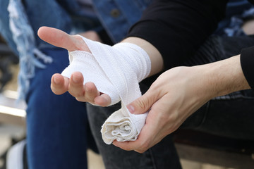 Close up of bandaging injured hand after an accident