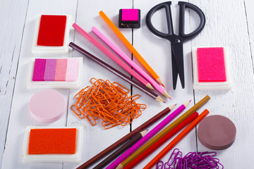red, pink, purple color pencils and paper clips, ink pads on white wooden table background