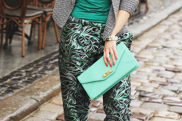 Stylish woman in a gray knitted cardigan and a green trousers