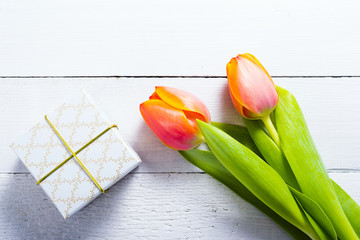 white gift box with tulip flowers on bright wood table