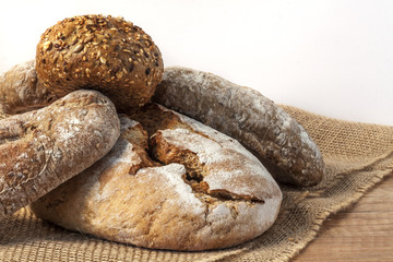 A loaf of bread and buns on a wooden table with a white wall in the background