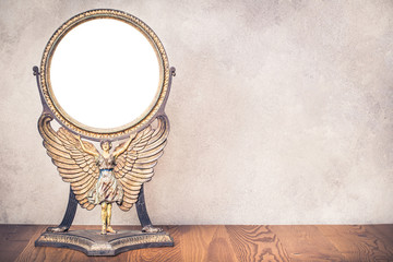 Old antique vintage cast iron desk makeup mirror frame blank holds on the stand in the form of goddess with wings or angel standing on table. Circa end of 1800s or early 1900s. Retro style filtered