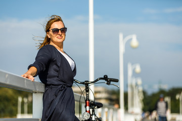 Woman relaxing with bike on pier