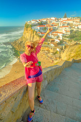 Happy sporty woman takes selfie of Azenhas do Mar on Atlantic Ocean. Tourist takes pictures by mobile phone with Portugal flag of Portuguese seaside resort near Colares. Tourism and travel in Portugal