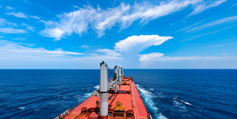 Indian ocean. Cargo ship moving towards skyline and beautiful clouds in calm sea