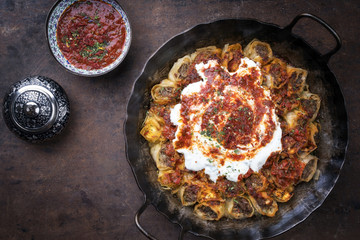 Traditional Turkey kolay yufka manti oven backed with lamb mincemeat as top view in a cast iron pan