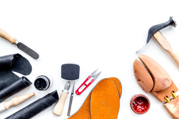 Work desk of shoemaker with instruments, wooden shoe and leather. White background top view copy space