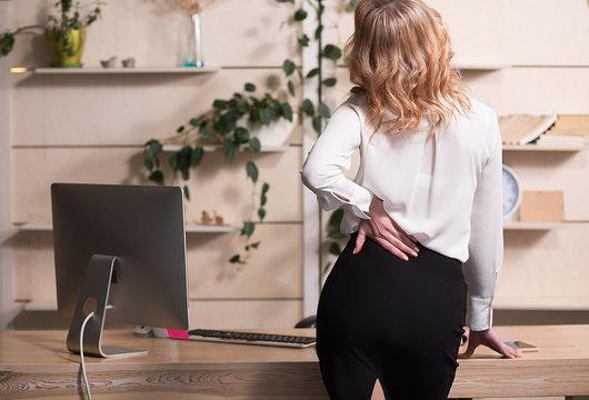 Businesswoamn in black skirt and white blouse making back massage . Having strong pain.