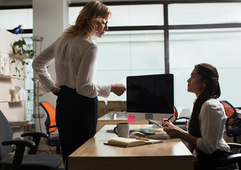 Side view image of female CEO standing at desk and giving directions to assistant.