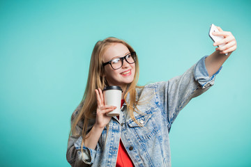 Beautiful blonde girl taking selfie with smile on blue background
