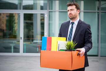 Businessman leaving his office after termination of employment
