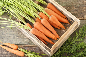 Fresh and ripe carrots in crate on wooden table