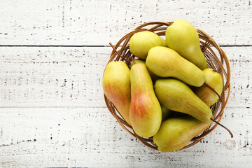 Ripe and sweet pears in basket on white wooden table