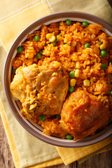 Galinhada is the Brazilian version of arroz con pollo chicken and rice close-up on a plate.Vertical top view
