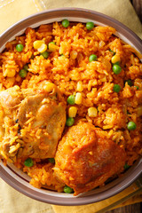 traditional spicy Brazilian food: chicken and rice close-up on a plate. Vertical top view