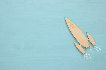 Top view image of wooden rocket toy over pastel background.