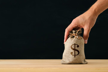 Male hand holding a sack of money over wooden desk.