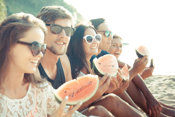 Friends eating watermelon on beach