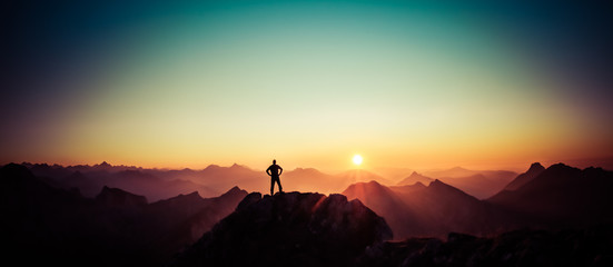 Man reaching summit enjoying freedom and looking towards mountains sunrise. Wall mural