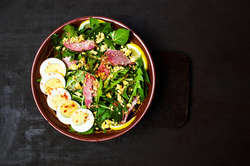 Dandelion salad with eggs meat and lemon in a bowl