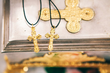 two golden crosses on a rope lay on a table