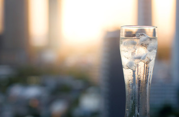 Transparent glass of ice water at cityscape building blur background. copy space image.