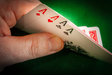 A player revealing a hand of four aces