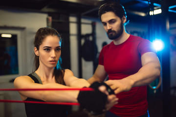 Instructor explaining to beautiful girl the best way of using rubber for stretching muscles