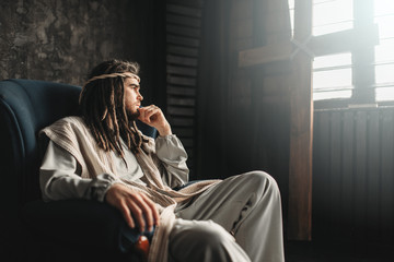 Thoughtful Jesus Christ sitting in a chair